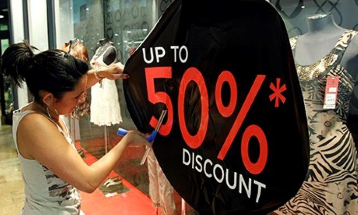 A woman sticks a discount sign on a shop window